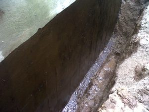 The waterproof rubber coating applied to exterior surface of a foundation wall prevents water from penetrating the wall